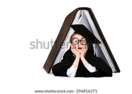 Cute student boy in graduation suit lying under the huge book. Educational concept. Isolated over white.  - stock photo