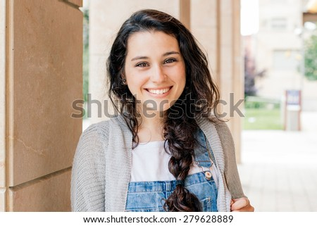 Cute student girl with braid smiling at you - stock photo