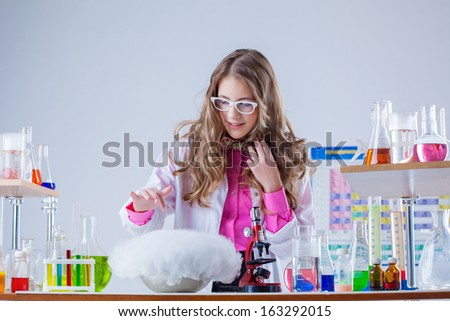 Cute student watching over experiment in lab - stock photo