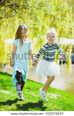 cute stylish little girls playing at park outdoor