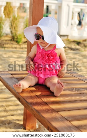 cute summer baby sitting on the beach - stock photo
