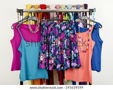 Cute summer outfits displayed on a rack. Wardrobe with colorful summer clothes and accessories. Floral skirt with matching tank tops. - stock photo