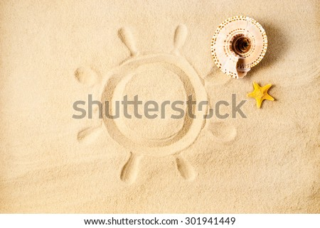 Cute summer sun drawing in the sand and few sea stuff. - stock photo