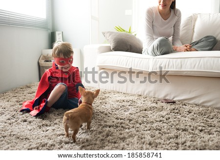 Cute superhero child and mother spending time together in the living room playing with dog. - stock photo