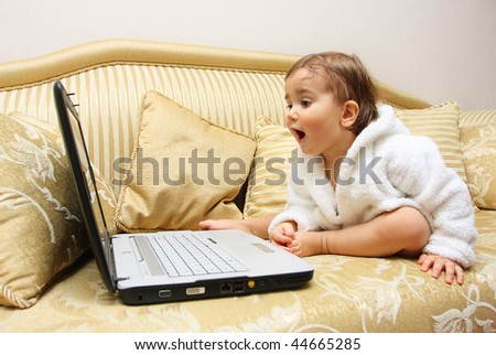 Cute surprised baby boy with laptop on sofa - stock photo