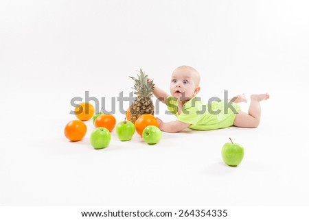 cute surprised baby looking fruit on white background including pineapple, oranges, apples. Photo with depth of field - stock photo