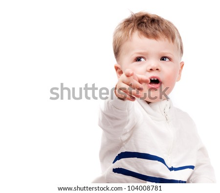 cute surprised baby pointing finger at us and looking to the side, isolated on white background