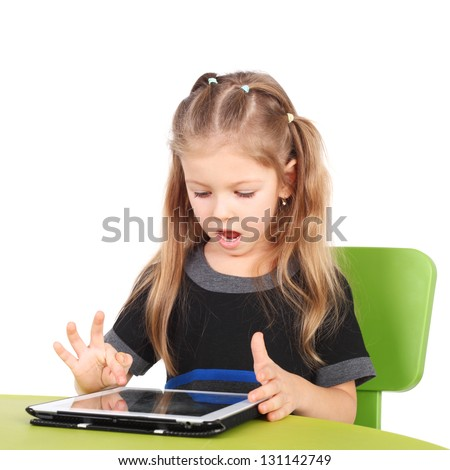 cute surprised little girl playing with the tablet PC - stock photo
