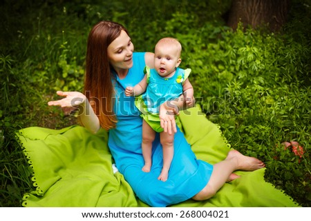 Cute Surprised Toddler Baby with Mom. Relaxing in green summer park.  - stock photo