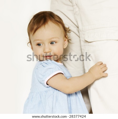 cute swarthy little girl holding her mother's legs, space for text - stock photo