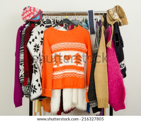 Cute sweaters displayed on a rack. Wardrobe with colorful winter clothes and accessories. - stock photo