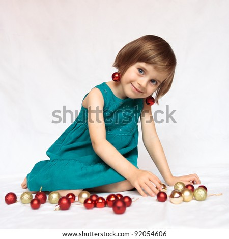 Cute sweet little girl playing with christmas decorations