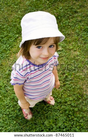Cute sweet little girl posing on the green grass