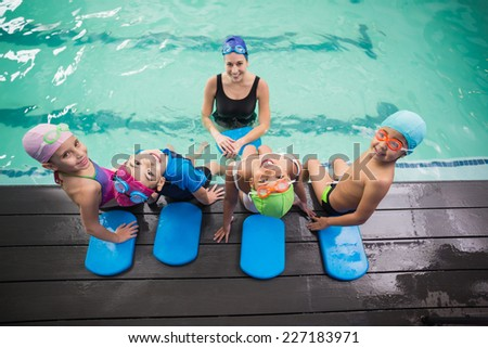 Cute swimming class and coach smiling at the leisure center - stock photo