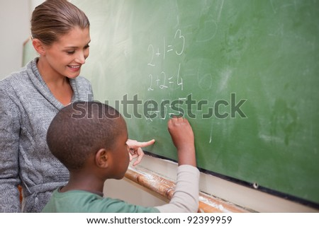 Cute teacher and a pupil making an addition on a blackboard