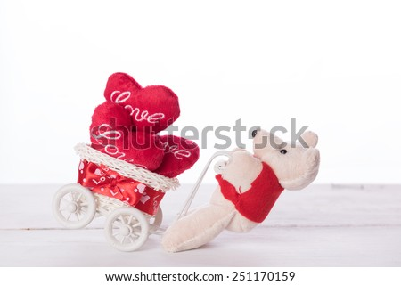 Cute teddy bear carry love heart items on white bicycle - stock photo