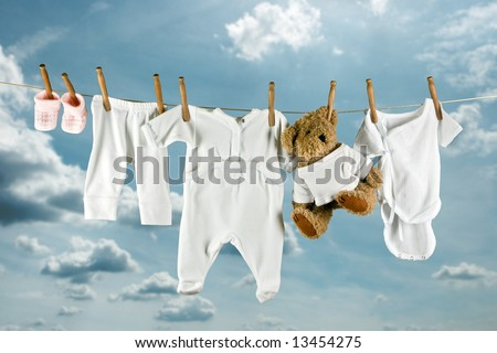 Cute teddy bear hanging outside between baby laundry - stock photo