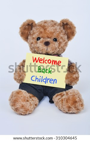 Cute teddy bear holding a yellow Welcome back children sign isolated on a white background