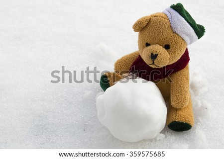 Cute teddy bear sits in the snow with a snowball  happy new year card christmas january winter snow white toy orange red brown green celebrate decoration new object day valentines gift still koronczi - stock photo