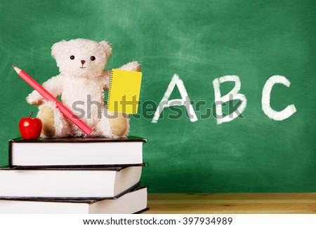 Cute teddy bear with a pencil,notebook,and apple sitting on the book in front of the blackboard. Kids study,school, education image. ABC alphabet on the chalkboard.  - stock photo