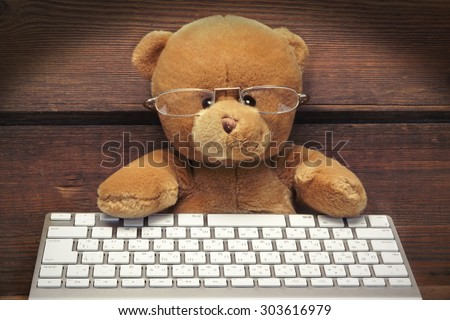 Cute Teddy Bear With A Wireless Keyboard In Front Of An Imaginary Computer Screen At Wooden Wall In Lanters Light. Internet Surfing Or Computer Work Concept - stock photo