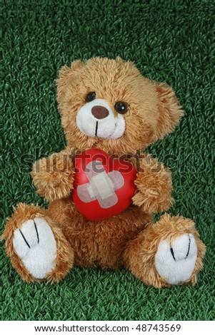 Cute teddy bear with decorative heart on green background