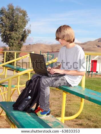 Cute teen aged boy sitting on bleachers working on his laptop. - stock photo