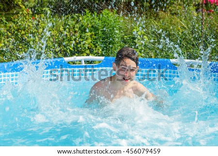Cute teen boy enjoying summer splashing water in a swimming pool