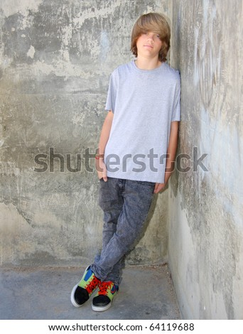 Cute teen boy leaning against a cement wall. - stock photo