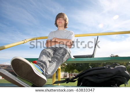 Cute teen boy sitting on bleachers with his laptop and backpack. - stock photo