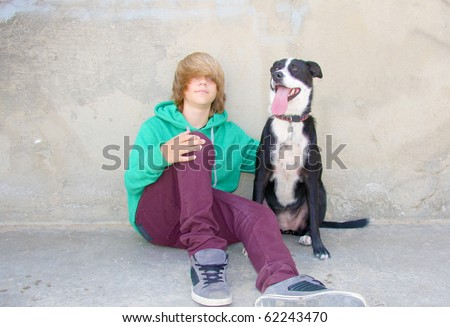 Cute teen boy sitting with his black dog against a cement wall. - stock photo