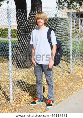 Cute teen boy standing in front of chain link fence near school. - stock photo