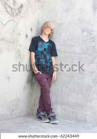 Cute teen boy with long shaggy hair standing against a cement wall with graffiti. - stock photo
