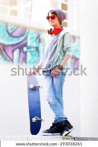 Cute teen boy with skateboard outdoors, standing on the street with different colorful graffiti on the walls, hipster style, cool teen fashion - stock photo