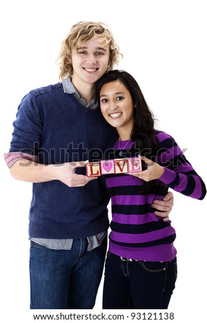"cute teen couple spelling ""love"" with blocks - stock photo"