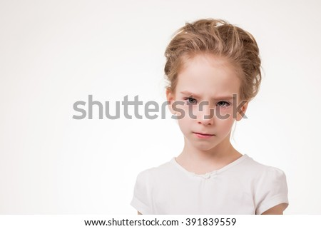 Cute teen girl angry frowns, studio portrait isolated on white background. - stock photo
