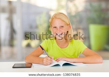 cute teen girl doing homework at home - stock photo