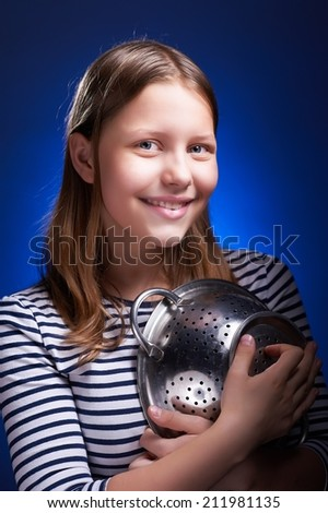 Cute teen girl holding colander and smiling - stock photo