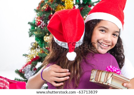 cute teen girl hugging mother on Christmas day - stock photo