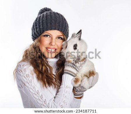 Cute teen girl in a knitted hat and sweater holding rabbit in her hands, close-up portrait - stock photo