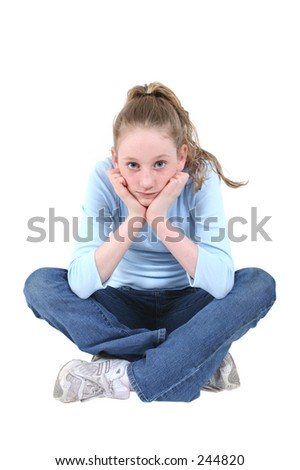Cute teen girl in blue and denim casual wear holding her face and looking bored or like she is watching TV.