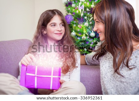 Cute teen girl receive gift from her beautiful young mother, happy family enjoying magical glowing present, spending Christmas holidays at home - stock photo