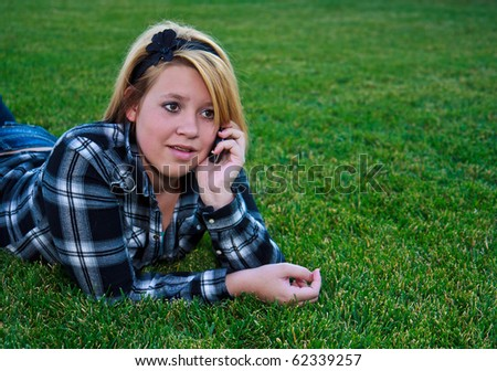 Cute teen talking on a cell phone the outdoors wearing plaid - stock photo