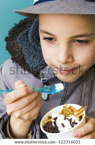 Cute teenage boy eating ice cream with chocolate topping - stock photo