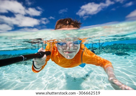 Cute teenage boy making selfie underwater in shallow turquoise water at tropical beach