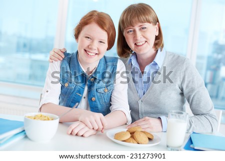 Cute teenage girl and her mother looking at camera with smiles during breakfast - stock photo