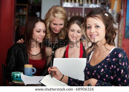 Cute teenage girl does homework with friends in a cafe