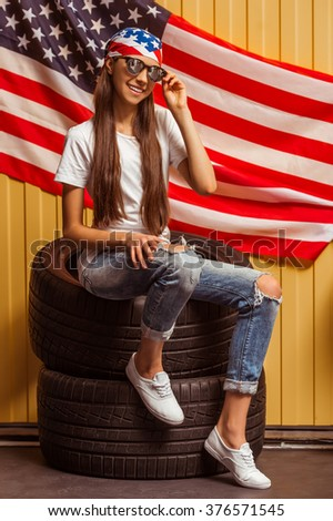 Cute teenage girl in a bandana and eyeglasses looking in camera and smiling, sitting on tires against orange background - stock photo
