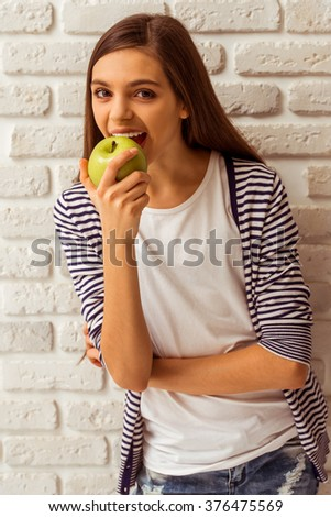 Cute teenage girl in casual clothes eating an apple, looking in camera and smiling, standing against white brick wall - stock photo