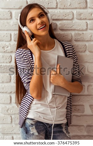 Cute teenage girl in casual clothes holding a tablet, listening to music and smiling, standing against white brick wall - stock photo